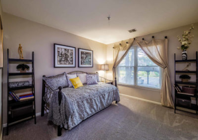 Spectacular model bedroom with carpeted flooring and large window in Pointe North apartment for rent