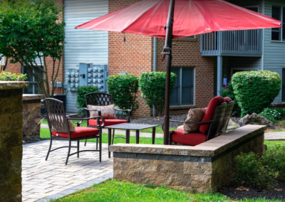 Communal outdoor seating area with red cushion chairs and parasols at Pointe North apartments in Bethlehem, PA